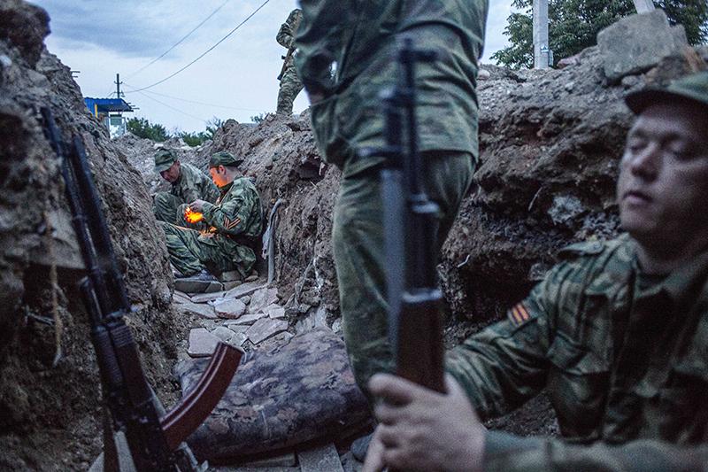 Des soldats séparatistes dans une des tranchées du check point de Semenivka. La nuit commence à tomber alors que deux pro russes s'allument une cigarette. Semenivka. Ukraine. 19/05/2014