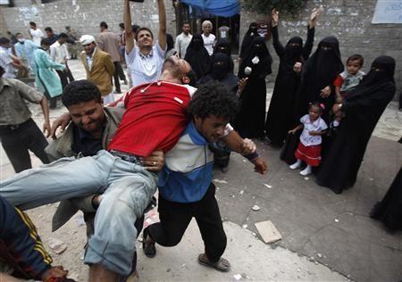 Evacuation d'un manifestant blessé à Sanaa. Cinquante-quatre personnes au moins ont péri en 48 heures lors de la répression du mouvement de contestation au Yémen où des fusillades acharnées ont éclaté lundi à Sanaa entre militaires passés dans les rangs des opposants au régime et soldats restés fidèles au président Ali Abdallah Saleh. (Reuters/Khaled Abdullah)