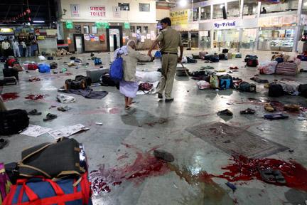 Un policier accompagne une victime, après la fusillade, dans la gare de Bombay, en Inde, le 26 novembre 2008. (Photo : Reuters)