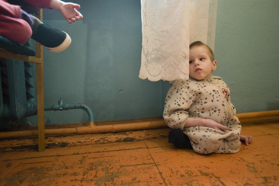 ©Gerd Ludwig (Vesnova, Biélorussie, 2005). Igor, 5 ans, est handicapé physique et mental. Il a subi des sévices émotionnels et il est sourd et muet. Isolé et anxieux, il passe le plus clair de son temps à se cacher derrière un rideau dans une maison pour enfants. L'institution pour enfants handicapés mentaux n'existerait pas sans le soutien de Tchernobyl Children International.