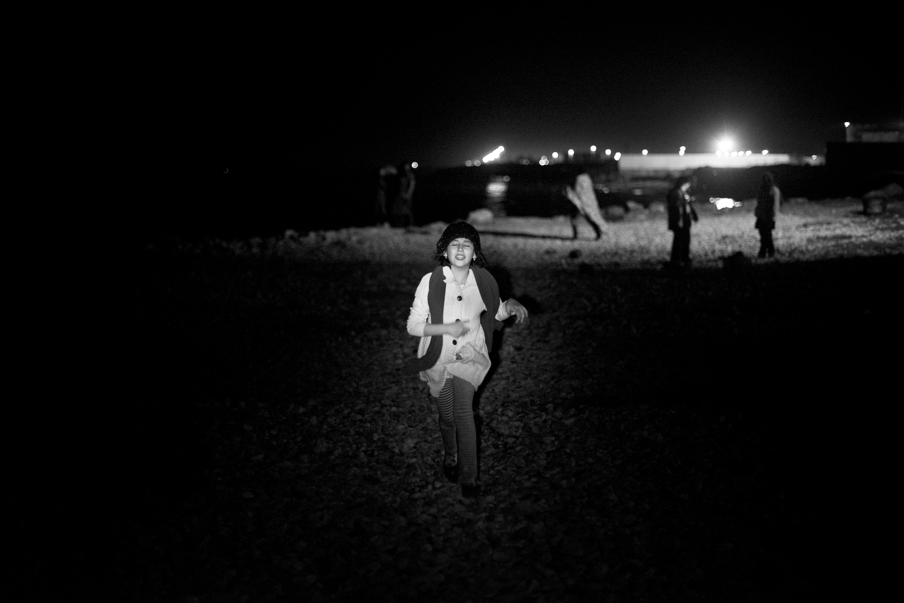 © Hashem Shakeri. 	(2014) Delnia, the 12 year old girl who has come to the beach with her family for fun. She is running toward the flashlight her father is shining at her. Babolsar, Iran