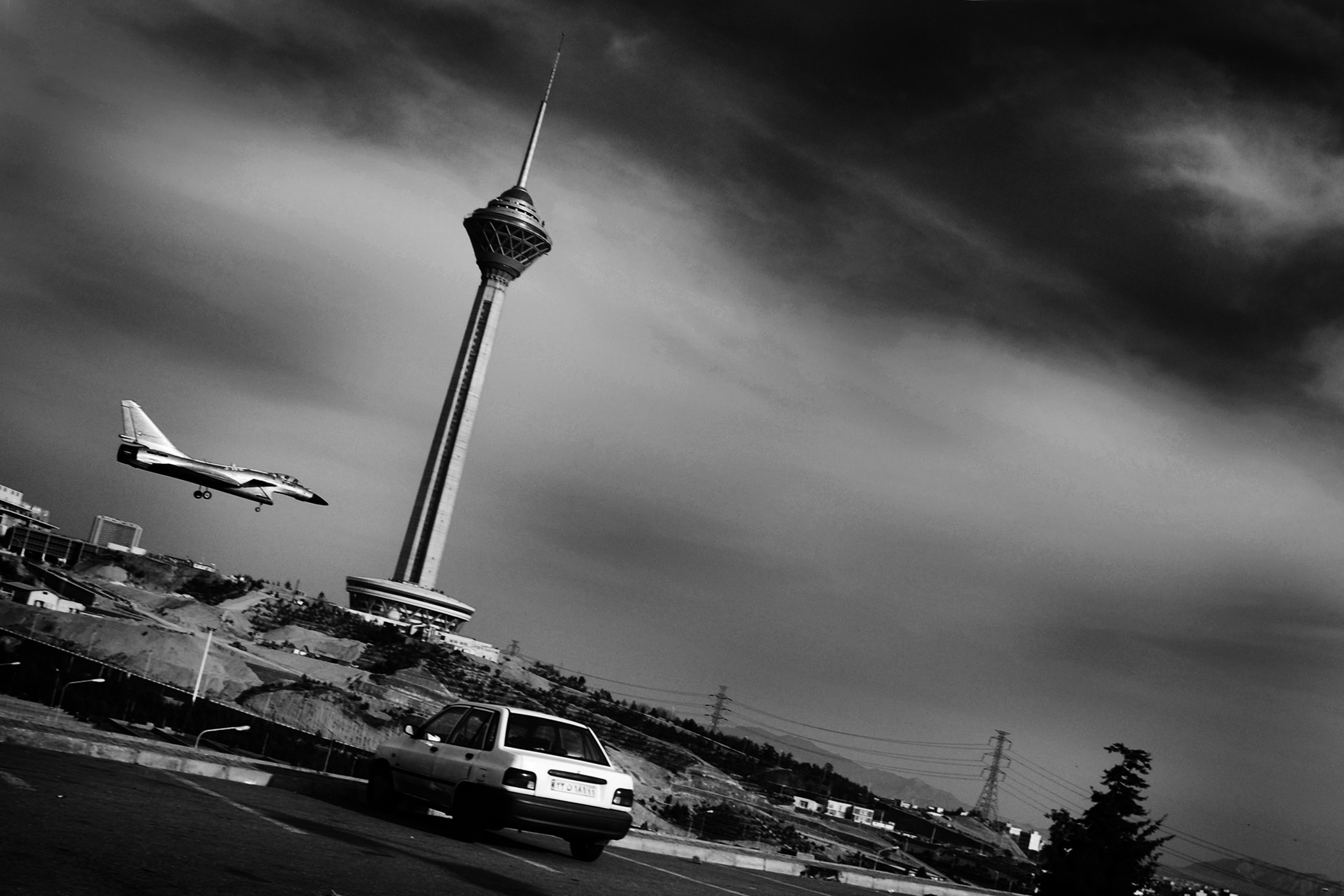 © Hashem Shakeri. (2011) A remote control plane passing by the tallest telecom Tower (Milad) in middle east. while forbidding the use of satellite dishes, the government confiscates all the dishes it can find in people's homes and signals noises in order to disrupt the broadcast of satellite channels and programs. These are done, Iranian officials claim, in order to fight against obscenity; however, the channels that are blocked are mainly those that broadcast political news. After the 2010 presidential elections, noise transmission increased greatly. Inside and outside Iran, people have protested widely - albeit to no avail - to noise transmission, specifically since it is believed to be harmful to health. Infertility and damage to the nervous system are among the most important conditions caused by noise transmission. Milad tower in Tehran (the tallest tower of Iran) is used both for telecommunication and the signalling of noise. Tehran, Iran
