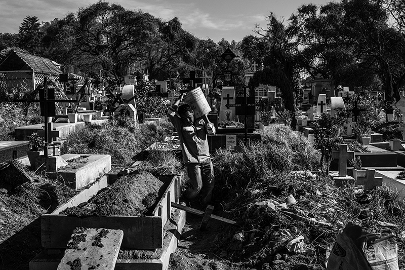 A worker of the San Lorenzo Tezonco cemetary is fixing a destroyed grave after it was hit by strong winds, Iztapalapa, Mexico City on March 15, 2016. The workers of the cemetary  employs their time to clean the hundreds path of the cemetary and dig graves. They also proceed to the exhumations of certain type of corpses.