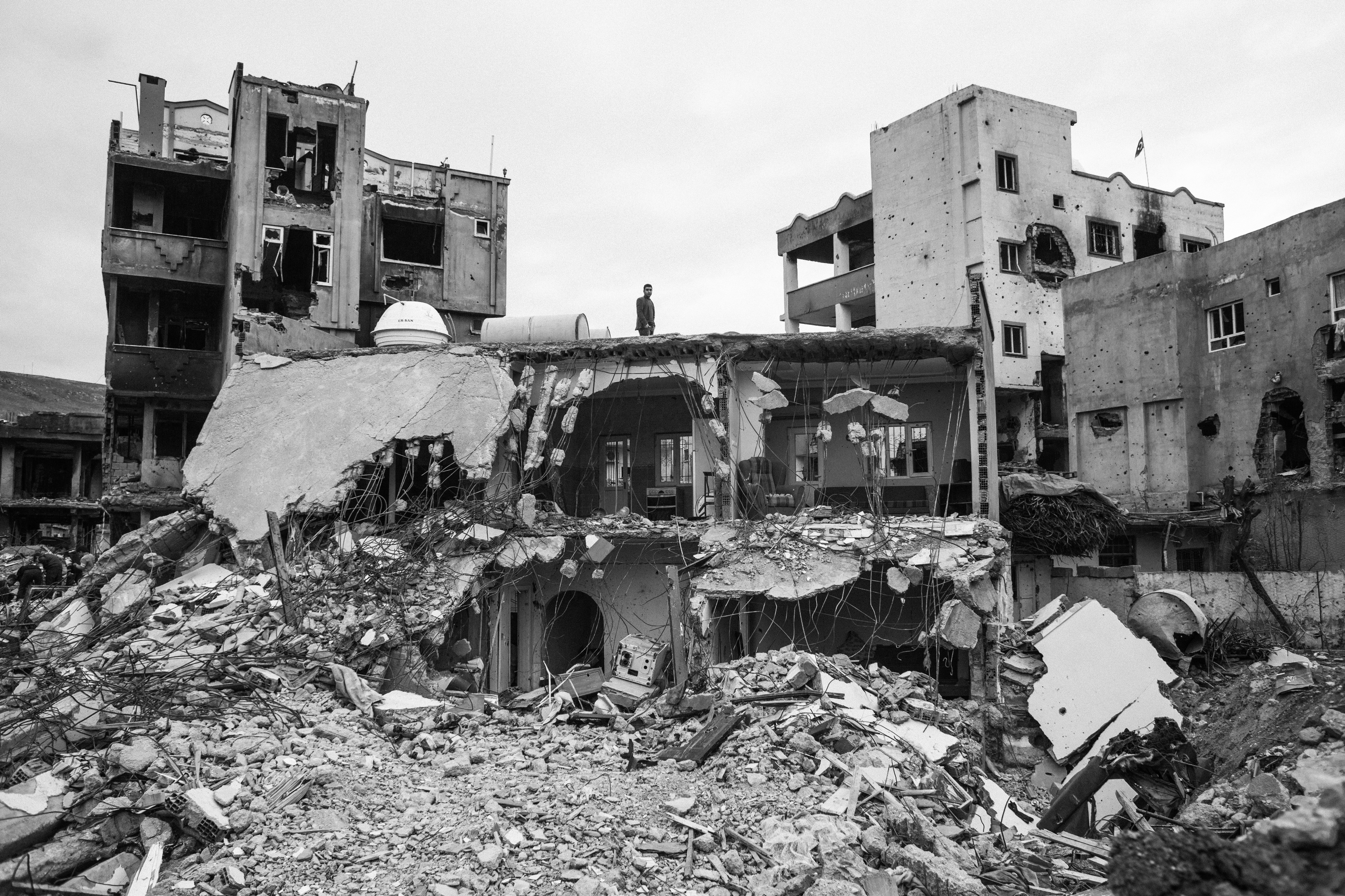 A man stands on his destroyed house in Cizre. Families returned to Cizre after a very long curfew. The clashes between the turkish government and PKK rebels left many homes in ruins. Families went back to Cizre after 78 days of curfew. In Cizre, 278 civilians have been killed during the clashes since july 2015. Cizre, Turkey, March 2016.