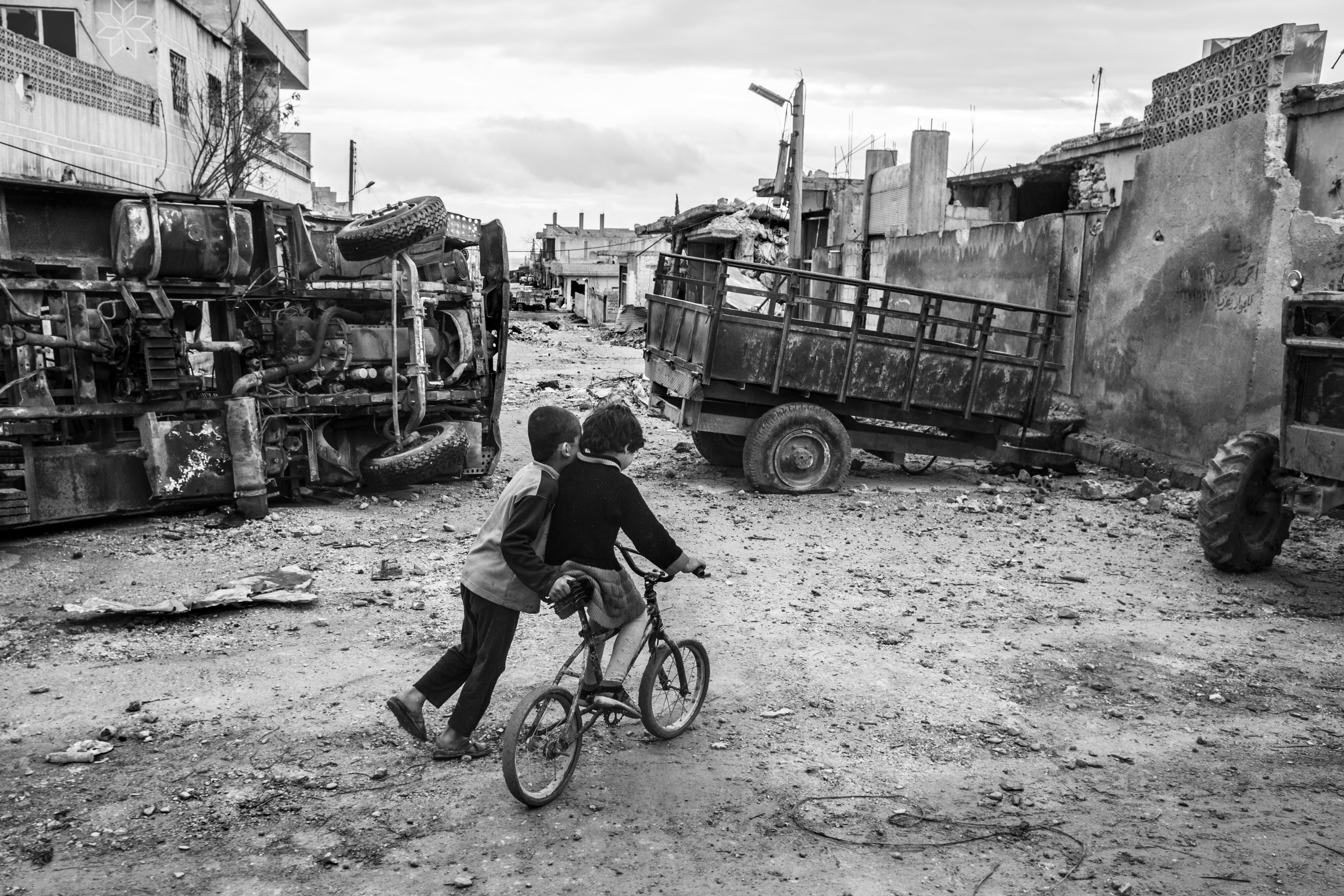 Children play in a street of Kobani. Life is slowly returning to normal in the streets of devastated city which experienced 133 days of fierce fighting. Kobani / Syria, March 22, 2015.