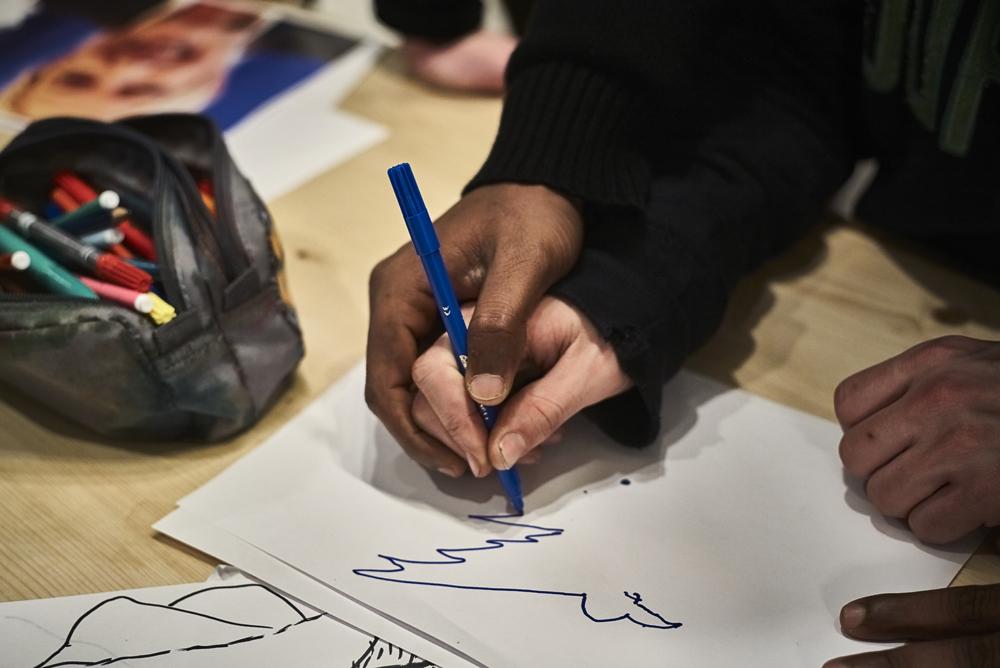 Un exilé aide Edouard un jeune français aveugle a réaliser un dessin